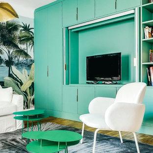 Immagine di un grande soggiorno chic aperto con libreria, pareti grigie, parquet chiaro, nessun camino, TV nascosta e pavimento marrone