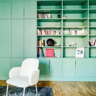 Ispirazione per un grande soggiorno classico aperto con libreria, pareti grigie, parquet chiaro, nessun camino, TV nascosta e pavimento marrone