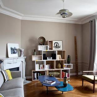 パリの中サイズのコンテンポラリースタイルのおしゃれな独立型リビング (ベージュの壁、無垢フローリング、コーナー設置型暖炉、ライブラリー、石材の暖炉まわり、テレビなし) の写真