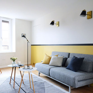 Cette photo montre un salon scandinave avec un sol en bois clair, aucune cheminée, un sol marron et un mur jaune.