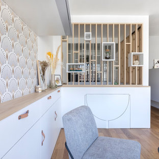 Small scandinavian open concept living room in Paris with white walls and plywood floors.