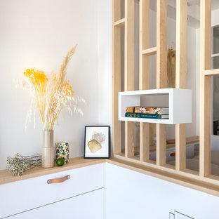 Kleines, Offenes Wohnzimmer mit weißer Wandfarbe und Sperrholzboden in Paris