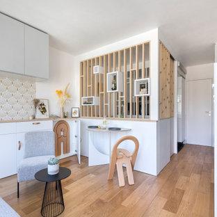 Modern inredning av ett litet allrum med öppen planlösning, med vita väggar och plywoodgolv