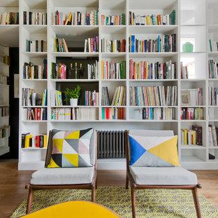 Inspiration pour un salon avec une bibliothèque ou un coin lecture nordique de taille moyenne et fermé avec un mur blanc, un sol en bois clair, aucune cheminée et aucun téléviseur.