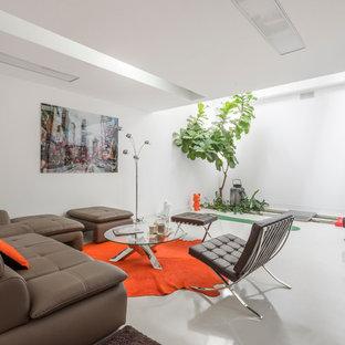 Réalisation d'un salon design ouvert et de taille moyenne avec un mur blanc, béton au sol, aucune cheminée et aucun téléviseur.
