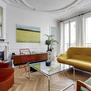 Aménagement d'un salon classique ouvert et de taille moyenne avec un mur blanc, un sol en bois clair, une cheminée d'angle et un téléviseur indépendant.
