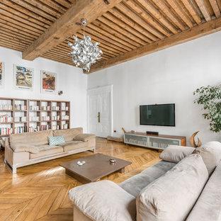 Réalisation d'un salon design de taille moyenne et ouvert avec un sol en bois clair, un téléviseur fixé au mur, un mur blanc et aucune cheminée.