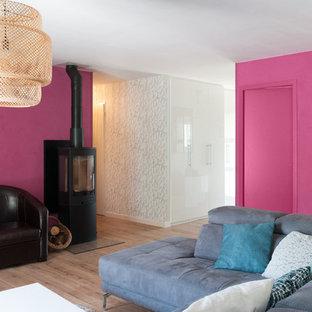 Diseño de salón abierto, actual, grande, con paredes rosas, suelo de madera clara y estufa de leña