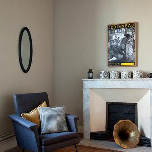 Cette image montre un salon vintage de taille moyenne et ouvert avec un mur beige, un sol en bois brun, une cheminée standard, un manteau de cheminée en pierre et aucun téléviseur.