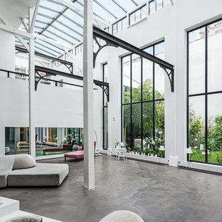 Idées déco pour un très grand salon industriel ouvert avec un mur blanc et béton au sol.