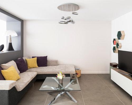 Cette image montre un grand salon design ouvert avec un mur gris, un sol en