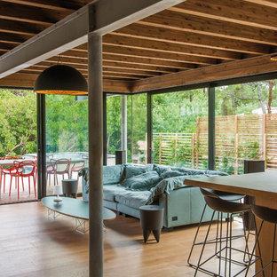 Cette image montre un salon design de taille moyenne et ouvert avec un sol en bois brun, aucune cheminée et aucun téléviseur.