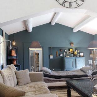 Esempio di un ampio soggiorno bohémian stile loft con pareti blu, pavimento in terracotta, camino classico, cornice del camino in pietra, nessuna TV e pavimento marrone