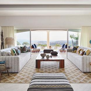 Réalisation d'un très grand salon marin ouvert avec une salle de réception, un mur blanc, un sol en travertin et un sol beige.