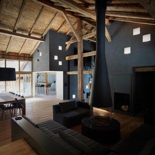 Idee per un soggiorno minimal con pareti nere, pavimento in legno massello medio, camino sospeso, cornice del camino in metallo e TV nascosta