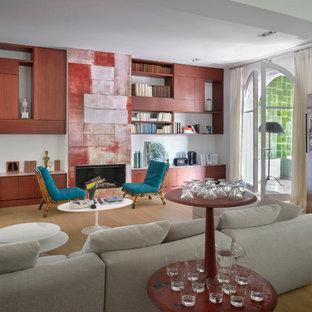 Cette image montre un grand salon avec une bibliothèque ou un coin lecture méditerranéen ouvert avec un mur blanc, un sol en bois clair, une cheminée standard et aucun téléviseur.
