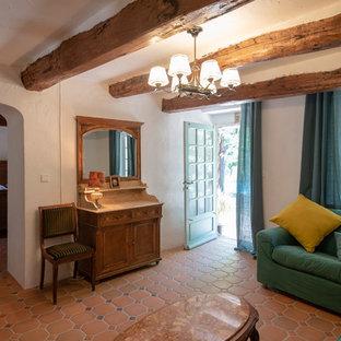 Aménagement d'un salon méditerranéen avec un mur blanc, un sol en carreau de terre cuite et un sol rouge.