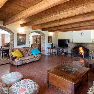 Cette photo montre un salon méditerranéen avec un mur blanc, un sol en carreau de terre cuite, une cheminée standard et un sol rouge.