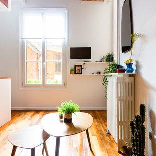 Idées déco pour un petit salon mansardé ou avec mezzanine industriel avec un mur blanc, un sol en bois brun, un sol marron, aucune cheminée et un téléviseur fixé au mur.