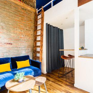 Aménagement d'un petit salon mansardé ou avec mezzanine industriel avec un mur blanc, un sol en bois brun, un sol marron, aucune cheminée et un téléviseur fixé au mur.