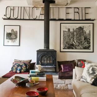 Inspiration pour un salon rustique de taille moyenne et ouvert avec un sol en bois brun, un poêle à bois, un mur blanc et aucun téléviseur.