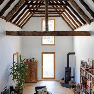 Réalisation d'un grand salon avec une bibliothèque ou un coin lecture champêtre ouvert avec un mur blanc, un sol en bois clair, un poêle à bois et un téléviseur indépendant.