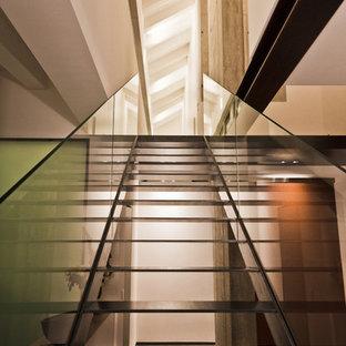 Foto di una scala a rampa dritta design con pedata in metallo, nessuna alzata e parapetto in vetro