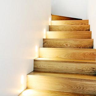 ミラノの中くらいの木のコンテンポラリースタイルのおしゃれな折り返し階段 (木の蹴込み板、金属の手すり) の写真