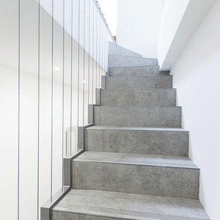 Ejemplo de escalera en L, actual, de tamaño medio, con escalones con baldosas, contrahuellas con baldosas y/o azulejos y barandilla de cable