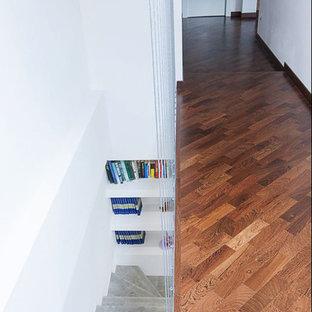 Imagen de escalera en L, actual, de tamaño medio, con escalones con baldosas, contrahuellas con baldosas y/o azulejos y barandilla de cable