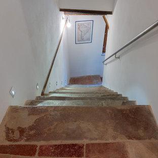 Ejemplo de escalera recta, rural, de tamaño medio, con escalones de piedra caliza y barandilla de metal