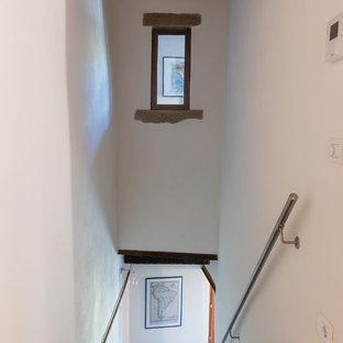 Ejemplo de escalera recta, rústica, de tamaño medio, con escalones de piedra caliza y barandilla de metal