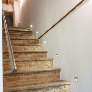 Foto de escalera recta, rural, de tamaño medio, con escalones de piedra caliza y barandilla de metal