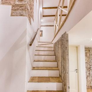 Esempio di una scala a rampa dritta country di medie dimensioni con pedata in terracotta e parapetto in legno