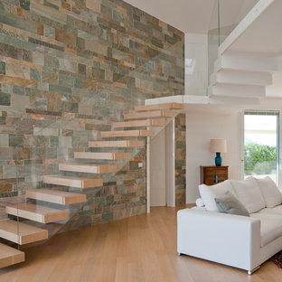 Imagen de escalera suspendida, actual, sin contrahuella, con escalones de madera y barandilla de vidrio