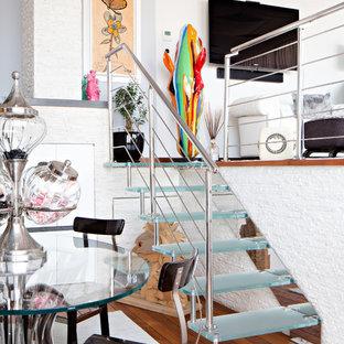 Immagine di una piccola scala a rampa dritta eclettica con nessuna alzata, parapetto in metallo e pedata in vetro