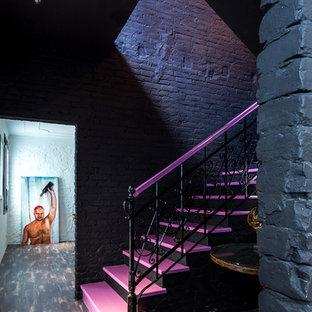 他の地域の中サイズのアクリルのエクレクティックスタイルのおしゃれな折り返し階段 (コンクリートの蹴込み板、金属の手すり) の写真