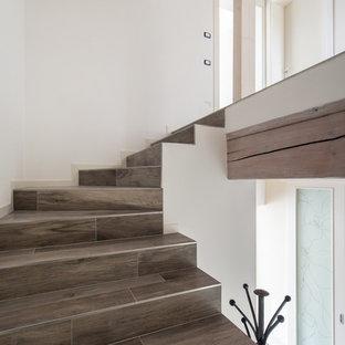 Foto de escalera en U, actual, con escalones con baldosas y contrahuellas con baldosas y/o azulejos