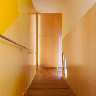 """Immagine di una scala a """"L"""" design di medie dimensioni con pedata in legno, parapetto in metallo e pareti in legno"""