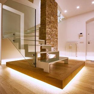 Imagen de escalera en L, contemporánea, de tamaño medio, con escalones de vidrio