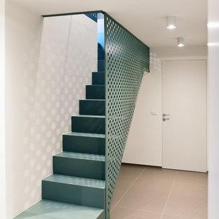 Modelo de escalera recta, actual, de tamaño medio, con escalones con baldosas, contrahuellas con baldosas y/o azulejos y barandilla de metal