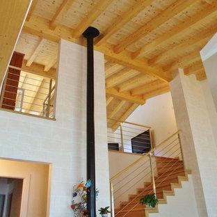 """Esempio di una grande scala a """"L"""" con pedata in legno, alzata in legno e parapetto in metallo"""