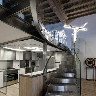 Imagen de escalera recta, urbana, grande, con escalones de metal, contrahuellas de metal y barandilla de vidrio
