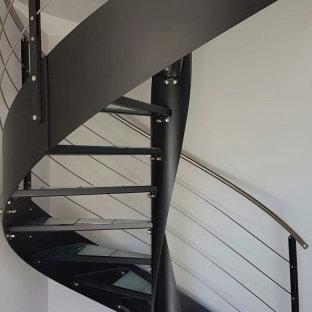 Foto di una grande scala a chiocciola con pedata in vetro, nessuna alzata e parapetto in metallo