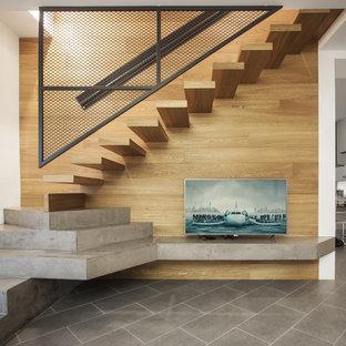 """Immagine di una scala a """"L"""" minimal di medie dimensioni con pedata in legno, nessuna alzata e parapetto in metallo"""