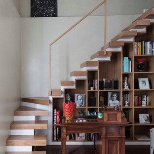 Imagen de escalera en L, actual, grande, sin contrahuella, con escalones de madera y barandilla de vidrio