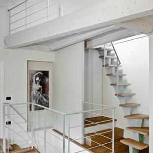 """Immagine di una piccola scala a """"L"""" minimal con pedata in legno e nessuna alzata"""