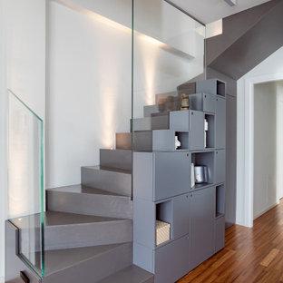 """Immagine di una scala a """"L"""" design di medie dimensioni con pedata in cemento, alzata in cemento e parapetto in vetro"""