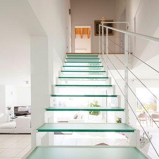 Idee per una scala a rampa dritta minimal di medie dimensioni con pedata in vetro