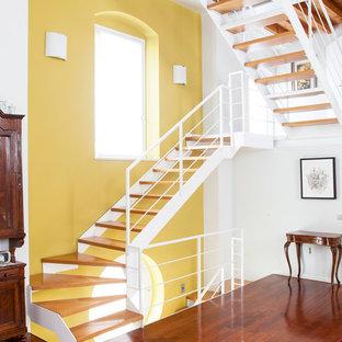 Cette photo montre un grand escalier sans contremarche méditerranéen en U avec des marches en bois et un garde-corps en métal.